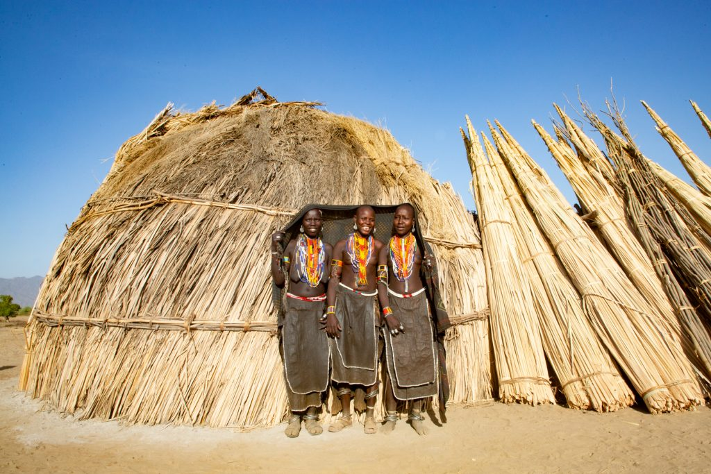 Arbore girls stand in front of their hut near Lake Chew Bahir